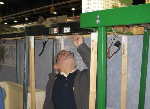 Il mitico Maesto Modellista Mario Malinverno alle prese con le connessioni elettriche sotto il plastico ASN a Verona Model Expo 2013. Si possono notare i cavi di interconnessione tra i moduli.