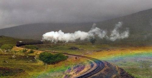 Un treno a vapore passa sotto l'arcobaleno - Foto CC Alan Mitchell da wikimedia