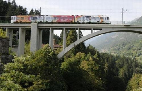 Il Dolomiti Express, convoglio con ampio spazio per biciclette a bordo, scavalca la profonda forra del fiume noce sul ponte di Santa Giustina- Foto da http://www.rincoboys.org