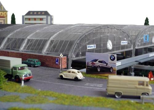 La copertura in vetro e acciaio della stazione di testa, affiancata da una strada. Foto da www.modellbahn-traumanlagen.de