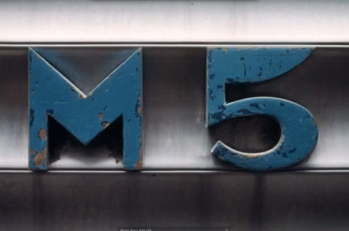Cifra identificativa della M5, rilievo metallico in colore blu - foto © Federico Centola, tratta da youtube