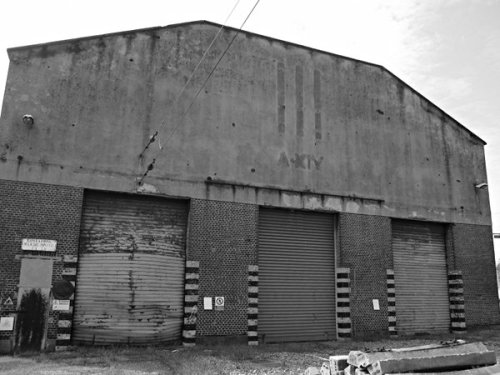 """La rimessa degli autotreni ATR 100 del deposito di Torino Smistamento. Venne costruita nel 1935, in pieno periodo fascista: infatti è ancora visibile l'iscrizione """"A. XIV"""" e l'impronta dei tre fasci littori. Da delta-november.it"""
